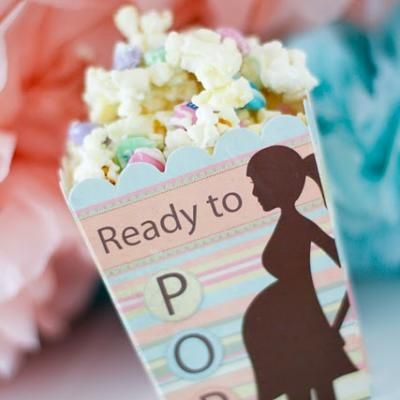Baby shower favors. popcorn with m's and melted white chocolate morsels. Cute
