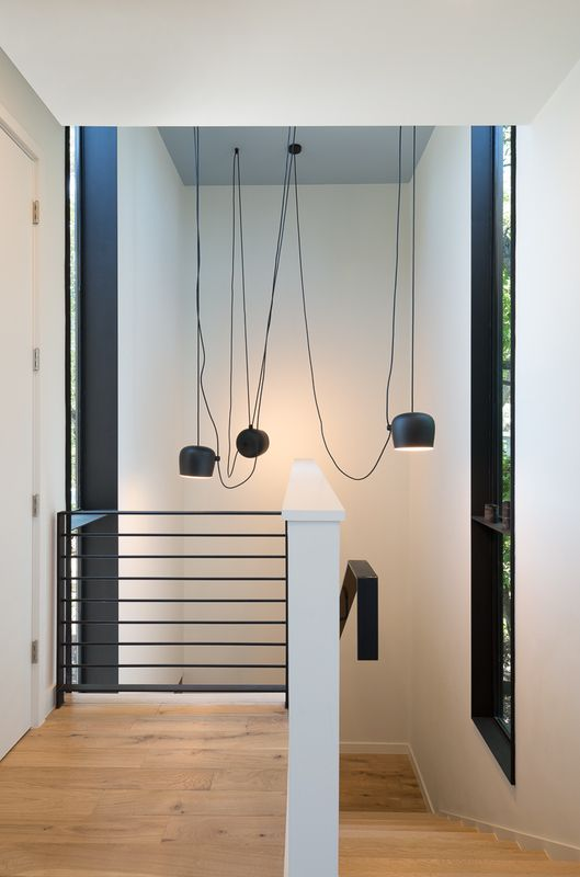 Bercy Chen Studios lights a stairwell with AIM pendant lighting in this modern home.