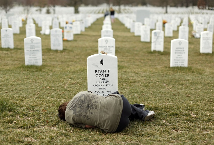 Lesleigh Coyer, 25, of Saginaw, Michigan, lies down in front of the grave of her brother, Ryan Coyer, who served with the U.S. Army in both Iraq and Afghanistan, at Arlington National Cemetery in Virginia March 11, 2013
