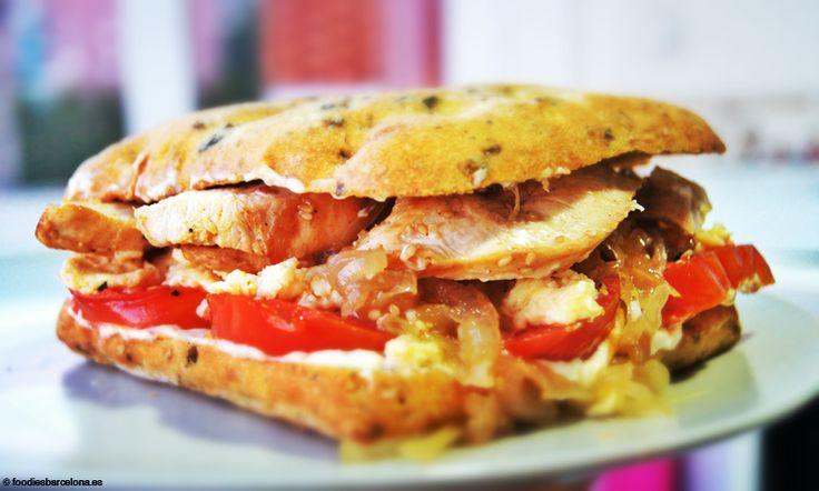 Sandwich con pan de focaccia y olivas negras, de pollo con huevos revueltos, cebolla caramelizada y tomates macerados en ajo y perejil.