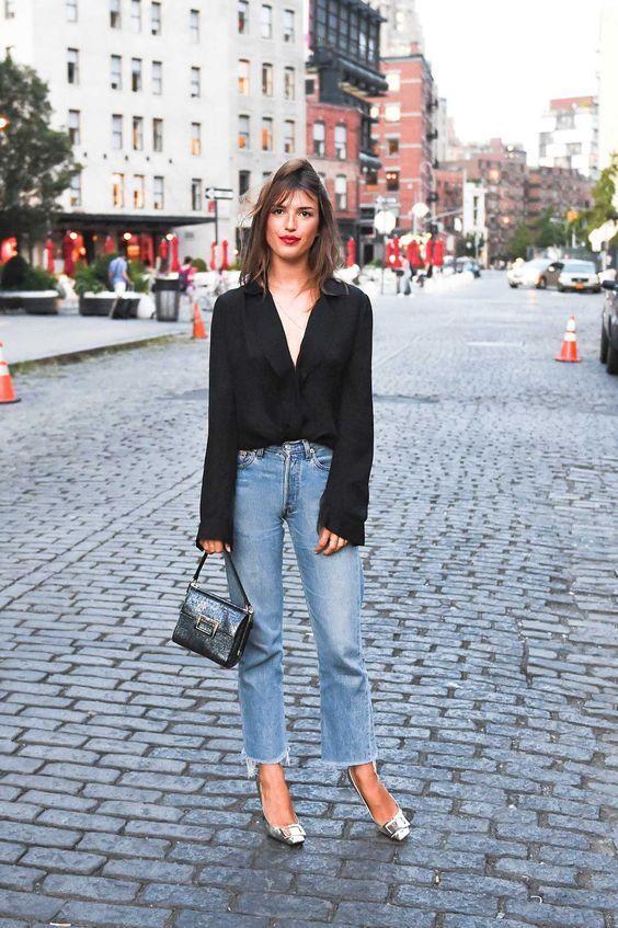 Jeanne Damas com camisa preta, jeans vintage, scarpin metalizado, bolsa de mão preta, batom vermelho, estilo das francesas, musas de estilo francesas