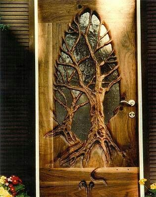 This unique door has two trees hand carved into the wood- certainly a work of art.  wood carvings. door art. beautiful doors.