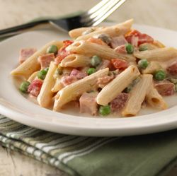 Creamy Ham and Penne Pasta:       8 ounces dry penne pasta, uncooked      1/2 cup frozen green peas      1 can (10 oz each) Ro*Tel® Mild Diced Tomatoes & Green Chilies, undrained      1 pkg (8 oz each) 1/3 less fat cream cheese (Neufchatel), cubed      1/2 cup shredded sharp Cheddar cheese      3/4 cup chopped fully cooked lean ham