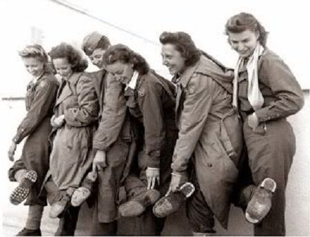 Flight nurses of the 807th Medical Air Evacuation Transport Squadron show their worn-out shoes after returning to Italy, 9 January 1944.