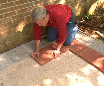 Begin laying the pavers against the house, making sure each one is even and the top surface is flush with the string.