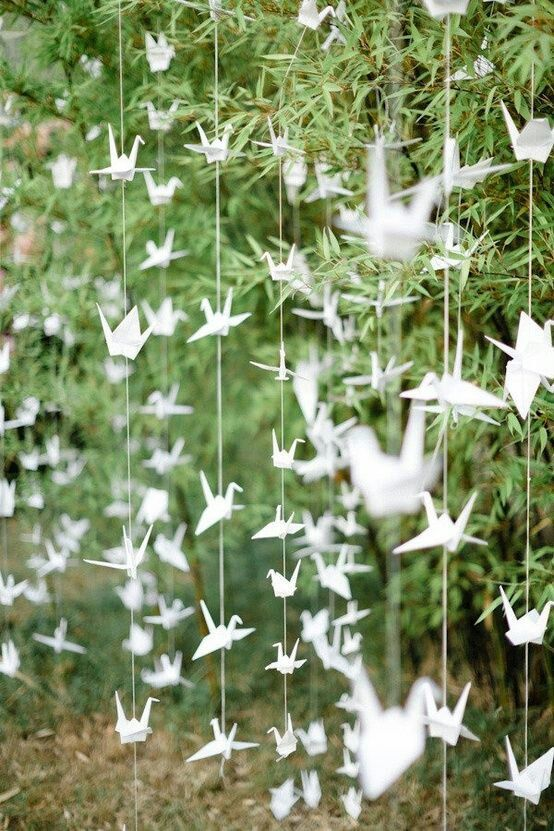Origami cranes strung through the trees for an outdoor wedding. Whimsical and beautiful!