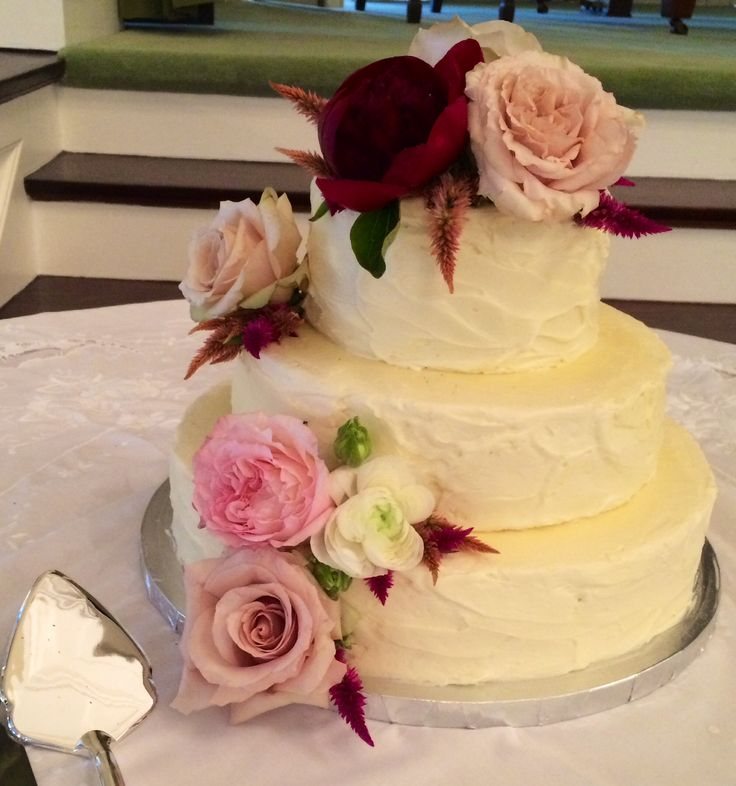 beautiful little wedding cake is dressed with cascading flowers of red charm peony, quicksand rose, Kiera garden rose, white ranunculus, pink celosia, and peach celosia