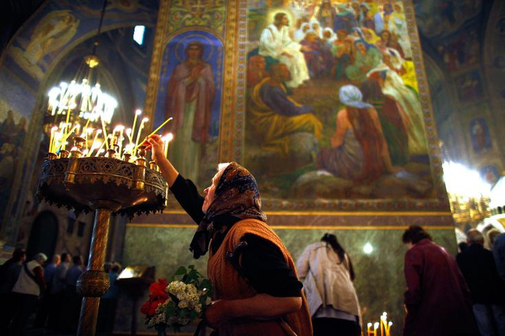 A worshipper lights a candle as she attends Sunday Mass led by Patriarch of Moscow and All Russia Kirill and Bulgarian Patriarch Maxim in Alexander Nevski cathedral in Sofia. (Stoyan Nenov/Reuters)