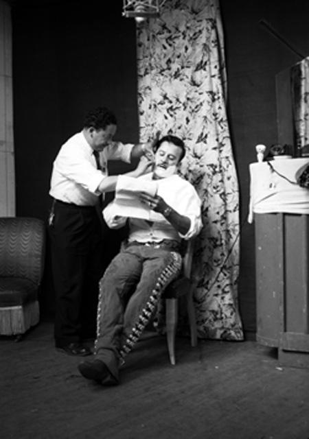 Pedro Infante Cruz lee un guión en su camerino mientras un barbero lo rasura.