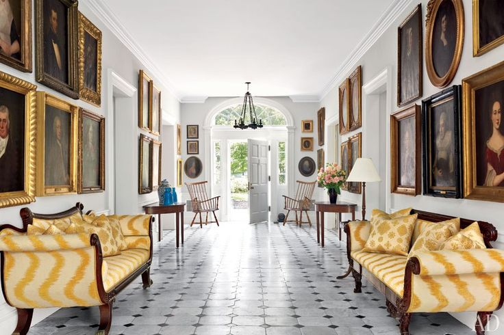 The entry hall of Alison Spear's historic Hudson Valley estate is populated by family portraits. The settees are clad in a Scalamandré flame stitch.