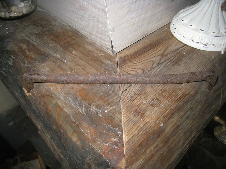 Gamle hjørnejern som feste sammenføying av gammelt tømmer på peishylle
