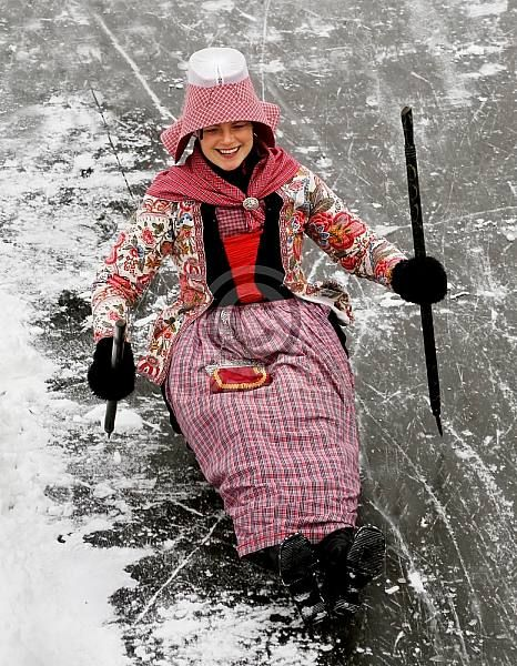 Europe | Portrait of a woman wearing traditional clothes, a traditional hat and sledging, Hindeloopen, Friesland, The Netherlands