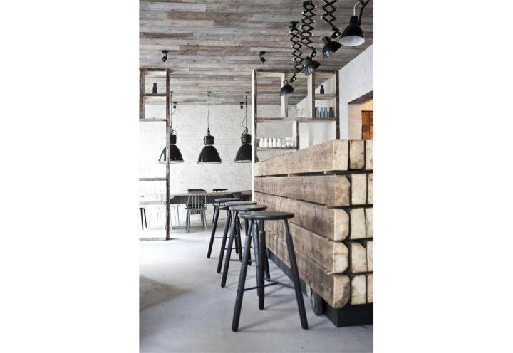La sala principale del ristorante danese Höst, realizzato da Norm Architects a Copenhagen, ospita una serie di tavoli e un bancone centrale realizzato con vecchi pallet e legno di seconda mano. Parola d'ordine: naturalità