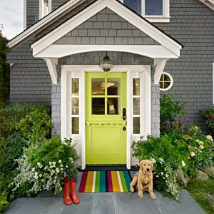 lime green front door set into a grey house with white trim. a rainbow rug sits in front of the door with a yellow puppy to one side, and red rubber boots on the other