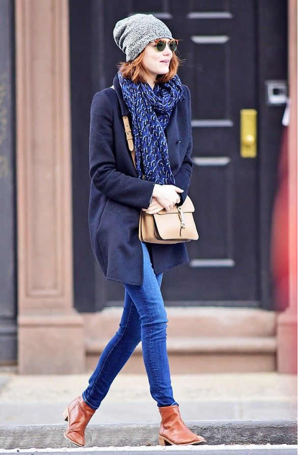 Emma Stone wears skinny jeans with a navy coat, navy scarf, gray hat, brown leather boots, and brown crossbody leather bag