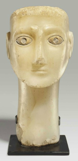 A SOUTH ARABIAN ALABASTER HEAD OF A MAN   CIRCA 1ST CENTURY B.C.-1ST CENTURY A.D.   With a long tapering neck and a thin oval face, the brows raised and arching slightly, his large eyes inlaid with contrasting white stone, the pupils once further inlaid, with a long, triangular nose, the thin lips straight, his sharp beard sculpted with the contours of the chin and cheeks, the top and back of the head roughly finished, with traces of plaster throughout