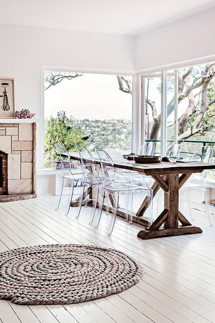Clear chairs offset a wooden kitchen table, putting a luxe spin on a woodsy interior. - HarpersBAZAAR.com