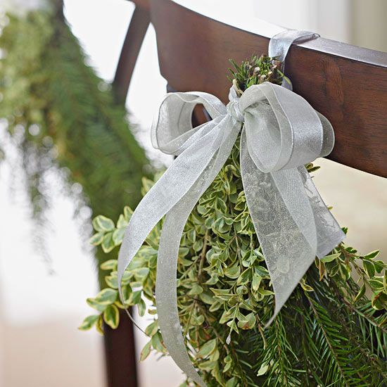 Christmas Chair Swags  small Christmas swags made from fresh greenery are festively tied to the back of dining chairs. Use florist's wire to bundle the greenery -- adding herbs, small flowers, or decorative branches -- to the bunch. Loop a ribbon around each chair back to tie the bouquet, adding the perfect finishing touch to your holiday table setting.