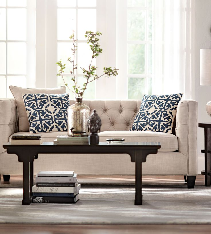 Little hints of blue and white can change the look of any space. These pillows pop on this tufted beige sofa. HomeDecorators.com #blueandwhite