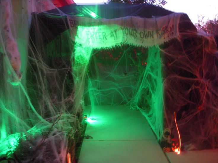 """Spiders Lair we created with a pop-up canopy frame, tree branches for the roof, about 10 bags of spider webbing, a """"boogy man"""" made from spray foam and paint, black sheets, about 100 spiders of all shapes and sizes, green uprights, and the cooperation from our neighbor to place it over the sidewalk to their house, which they had to go through each time they wanted to get to the front door."""