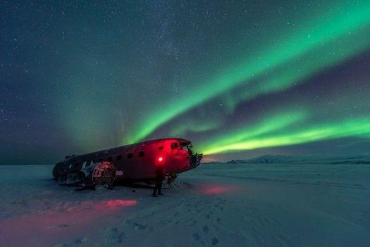Un'immagine che sembra provenire da un altro mondo: un uomo con una lampada frontale dal colore rosso appare alla luce di un'aurora. Ormai ridotto a un relitto, l'aereo, un Douglas DC-3 Super della Marina degli Stati Uniti, è stato costretto a fare un atterraggio di emergenza in Islanda. Tutti i passeggeri dell'aereo sono sopravvissuti all'atterraggio di fortuna.