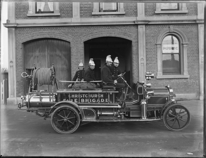 Sydenham Fire Brigade, Christchurch, shows unidentified firemen on fire truck outside an unidentified building
