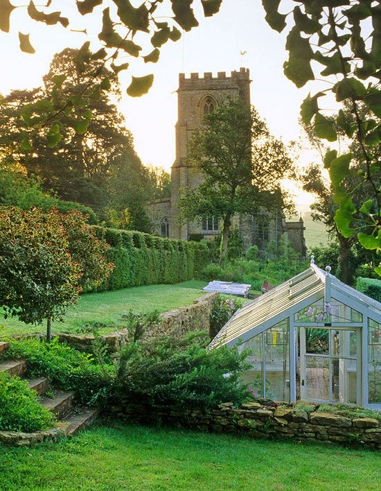 Greenhouse and Old Rectory Tower. Old Rectory, Netherbury, West Dorset, England  Conditions: Heavy clay and fertile sandy clay, mild and wet climate   Highlights: Classic English garden with exuberant plantings, formal topiary, and a memorable bog garden and thornery. Jerry Harpur for Traditional Home®