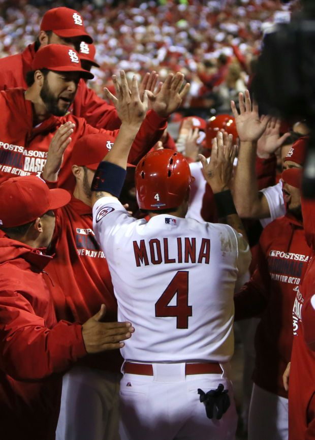 Yadier Molina is congratulated by his team after scoring in the third inning of Game 6 of the NLCS 10.18.13