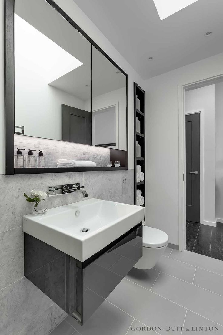 Bespoke dark wood and mirrored cabinet in master bathroom. Bespoke shelving unit. Wall-mounted taps on marble tiles. #GD&LBespoke