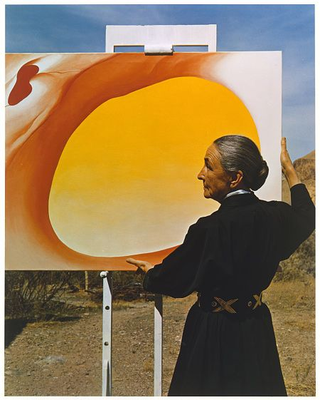"Georgia O'Keeffe, ca. 1960 / photo by   Michael A. Vaccaro / Chromogenic print  ""In this 1960 photograph, the artist, age seventy-three, poses next to her earlier canvas, Pelvis Series, Red with Yellow (1945)."" -- from the Met"