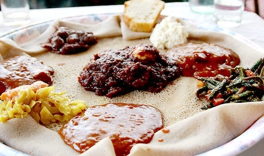 """Injera (crepe-thin bread-a staple in Ethiopian cuisine). The book Cutting for Stone describes it like this: """"The mark of a native is that your fingers are never stained by the curry; you use the injera as your tongs, as a barrier, while you pick up a piece of chicken or beef sopped in the sauce."""""""