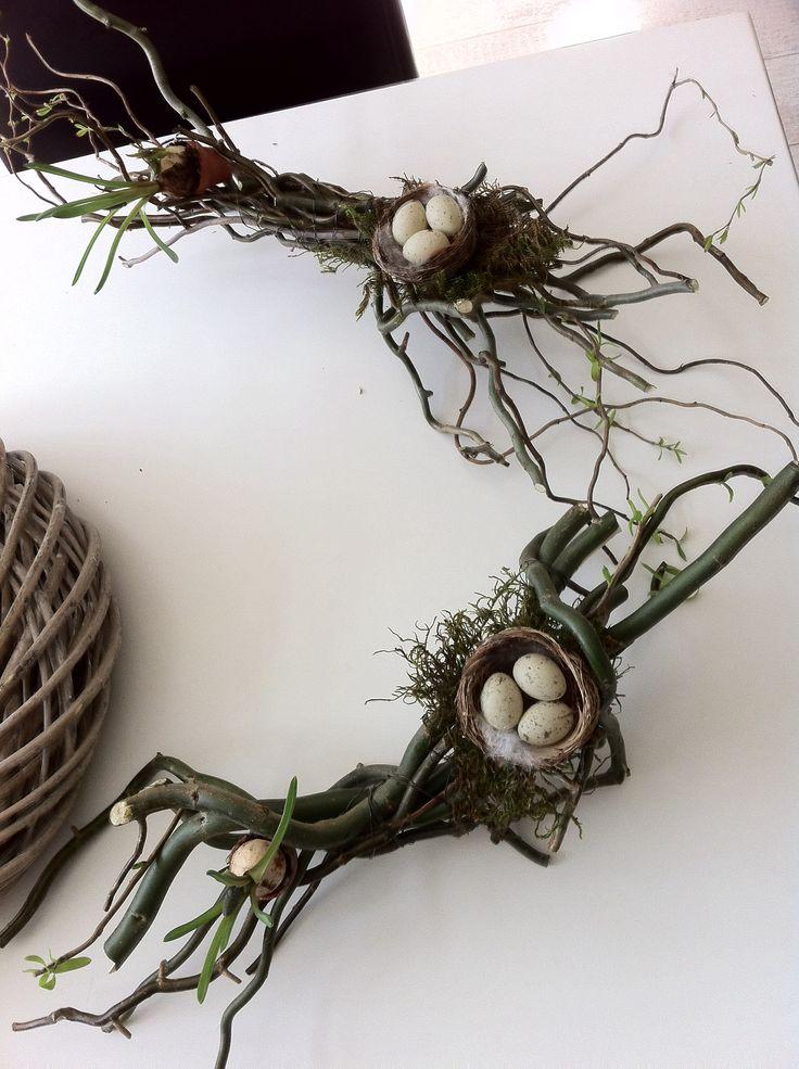 Een bosje paastakken ( restjes ) omwikkeld met binddraad , een nestje  met eitjes op een stukje mos geplakt en een klein bloempotje met een bloembolletje blauw druifje