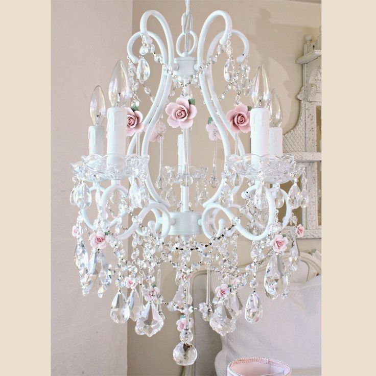 Inspired by centuries-old Fairy-tales' fantasy and romance, this 5-light white chandelier has been dressed to impress with LOADS of sparkly crystal prisms and fancy-cut glass bobeches! Spectacular blush-pink porcelain roses in full bloom make this chandelier a true vision of romance, elegant, sparkly and undeniably dreamy…