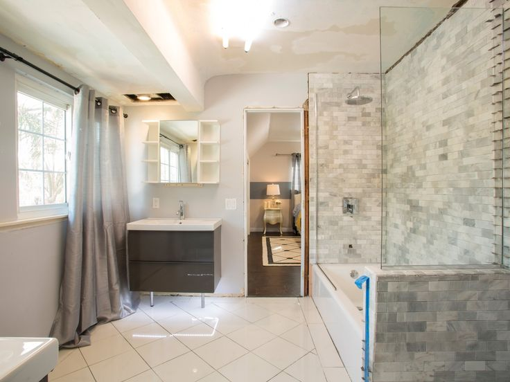 small modern bright bathroom after remodel with bathtub shower and small vanity