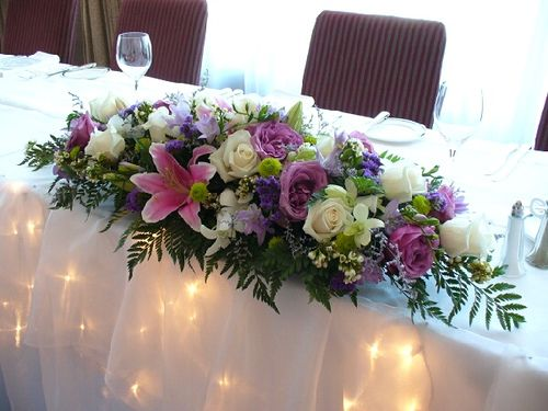Colorful Head Table Arrangement by floralbiz, via Flickr. I love the little white lights under the tablecloth!