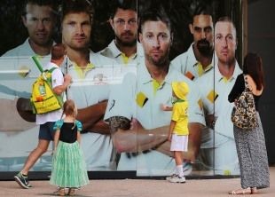 People look at posters of Australian players outside the Adelaide Oval two days before the first Test against India