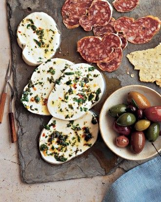 Antipasti platter with marinated mozzarella, olives, salami, crackers on a rustic slate tile.  This is one of my favorite go to's for casual entertaining