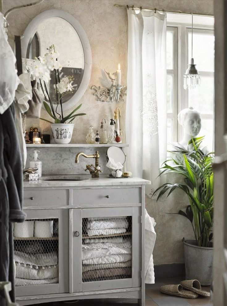 A dresser is repurposed and used as a bathroom vanity. I love the chicken wire on the door fronts.