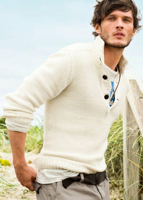 White sweater, tee, black belt & grey pants.