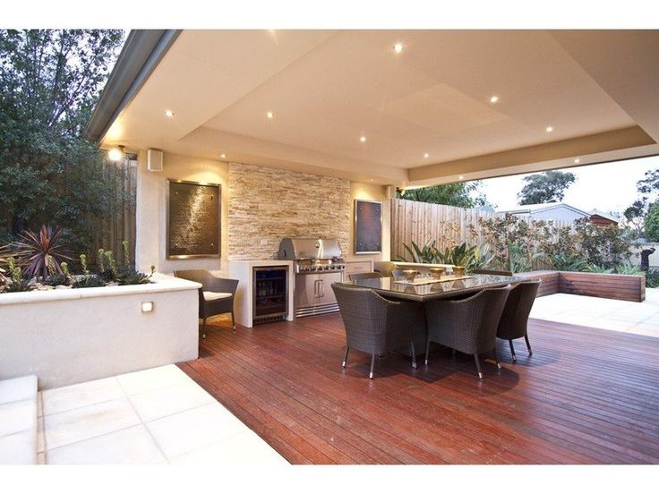 Walled outdoor living design with bbq area & decorative lighting using - Best outdoor kitchens and living area