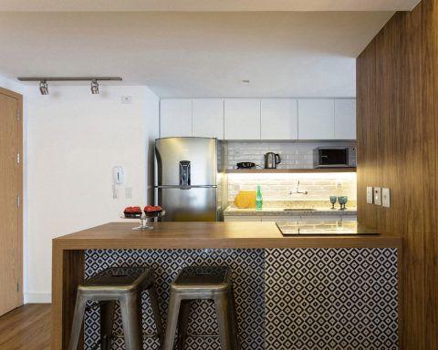 """A cozinha americana ganhou revestimento de cerâmica da Portobello, nas cores azul marinho e cinza. Já as banquetas da Tolix, feitas de aço galvanizado com pintura de pó, ao lado dos eletrodomésticos em aço inox, dão um ar urbano para o espaço. """"Queríamos um ponto focal. Para isso, colocamos um revestimento diferenciado que desse ênfase como pano de fundo"""", explica a arquiteta."""
