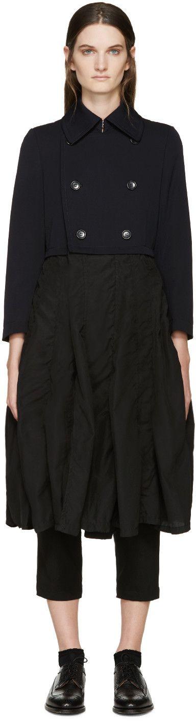 Manteau à manches longues en gabardine de laine bleu marine. Col classique. Double-boutonnage à l'avant. Jupe à panneaux en voile noir. Poches passepoilées à la taille. Non doublé. Coutures ton sur ton.