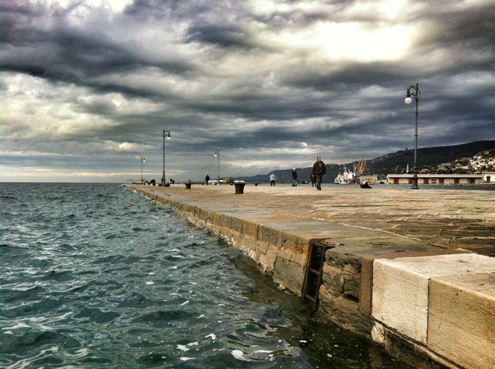 Guardò il fiume d'acqua che si riversava su Trieste, sferzata da forti refoli di bora e scosse il capo, ripensando a quanto dolore, orrore e terrore inutile era stato sparso in quella terra così vicina a loro.   Molo Audace