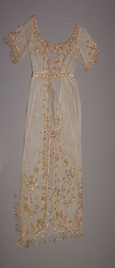 Dress Date: ca. 1912 Media: Silk Net With Metallic Embroidery And Beads Accession Number: X1989.1147 Low necked bodice, elbow length fringed sleeves and open front skirt all of gold beaded tulle. The embroidery placement is a la Matilde, as dresses of the early 19th century. (slip missing)