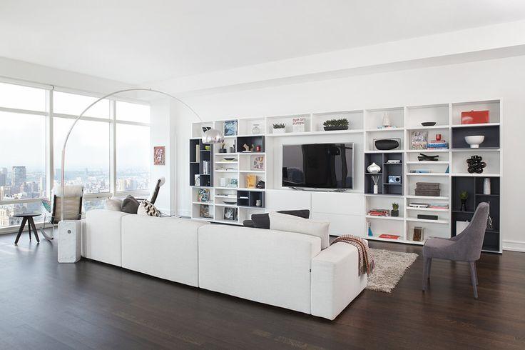 Salotto moderno molto luminoso, grande divano, libreria in bianco e nero e pavimenti in legno