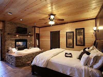 Romantic bedroom with a king size bed, jacuzzi tub and fireplace in the bedroom.