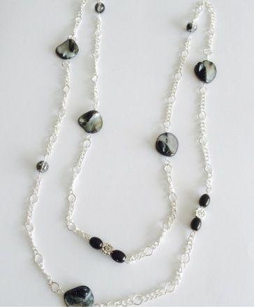 Collier sautoir noir et métal argenté. Sautoir avec chaîne en métal argenté d'une mi-longueur de 50 cm avec différentes perles :  - perles Nuggets 10-20 mm noires avec reflets gris - perles Crackle noires et transparentes  - perles noires avec petite perle en métal argenté