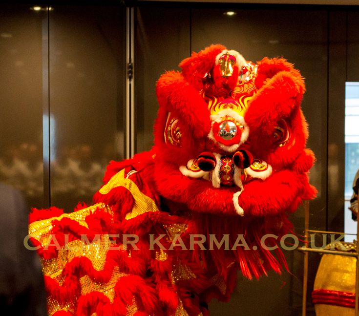Red Chinese Lion with live musicians and herder entertaining guests for Chinese New Year at this prestigious city bank in London. Available to hire LONDON, MANCHESTER, CHESHIRE, BRIGHTON, NEWCASTLE, BIRMINGHAM