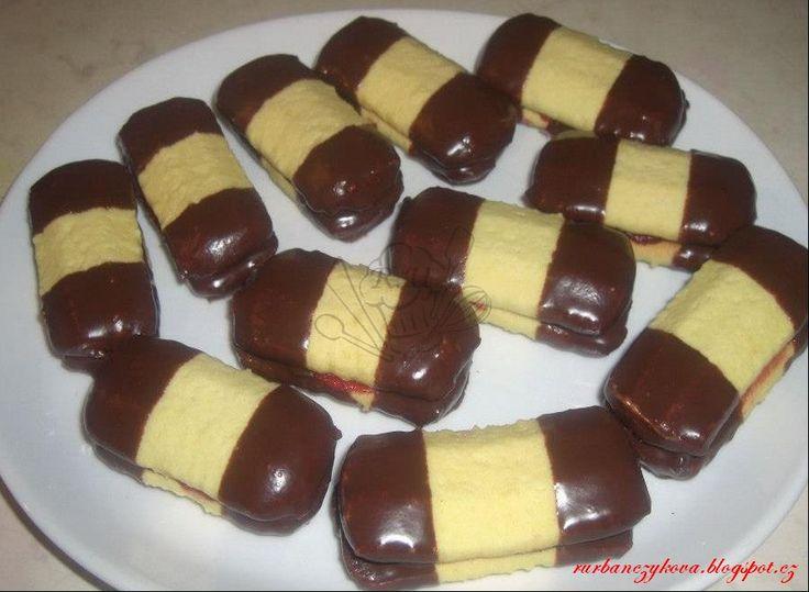 Třené cukroví-banánky Suroviny      Suroviny:     500g hladká mouka     270g moučkového cukru     370g másla     3 vejce     1 vanilkový cukr     1 prášek do pečiva     5 vanilkových pudingu     zdobení:     čokoláda na vaření     marmeláda