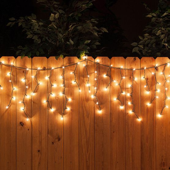 Clear icicle lights on green wire are perfect for hanging along wooden fence lines and across darker roofs and railings.